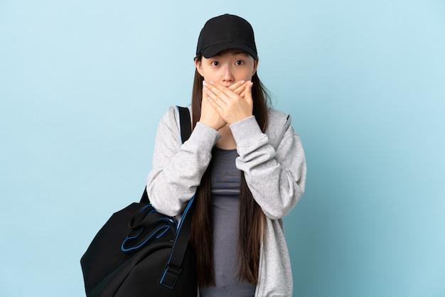 Junge sport-chinesin mit sporttasche über lokalisierter blauer wand, die mund mit händen bedeckt