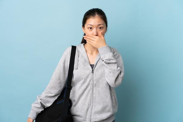 Junge sport-chinesin mit sporttasche über lokalisierter blauer wand, die mund mit hand bedeckt