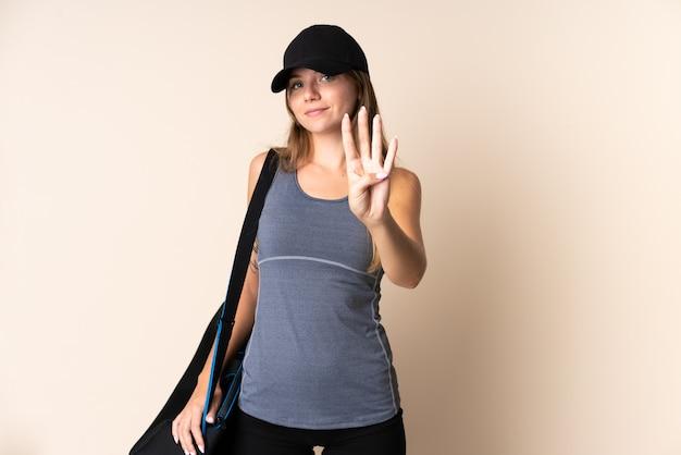 Junge sport litauische frau, die eine sporttasche lokalisiert auf beige glücklich hält und vier mit den fingern zählt