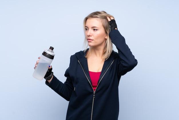 Junge sportblonde frau mit sportwasserflasche