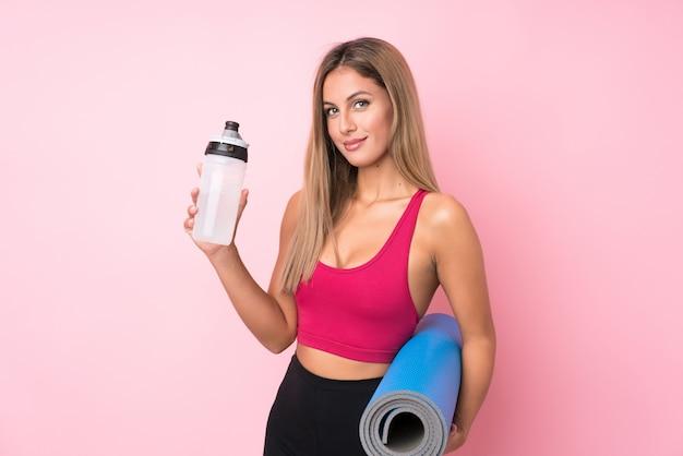 Junge sportblondine über lokalisiertem rosa hintergrund mit sportwasserflasche und mit einer matte