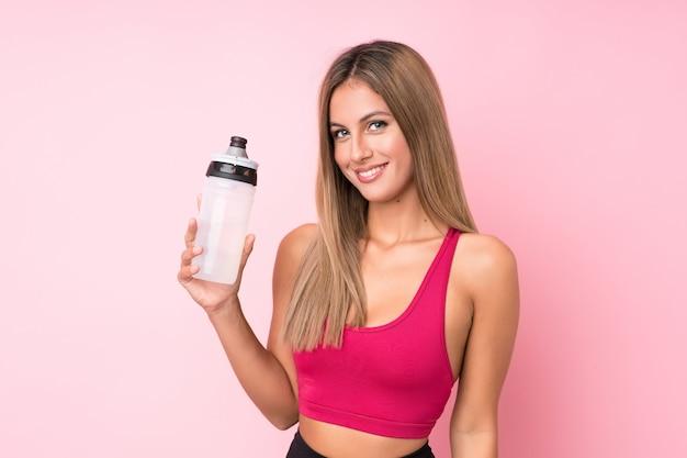 Junge sportblondine über lokalisierter rosa wand mit sportwasserflasche