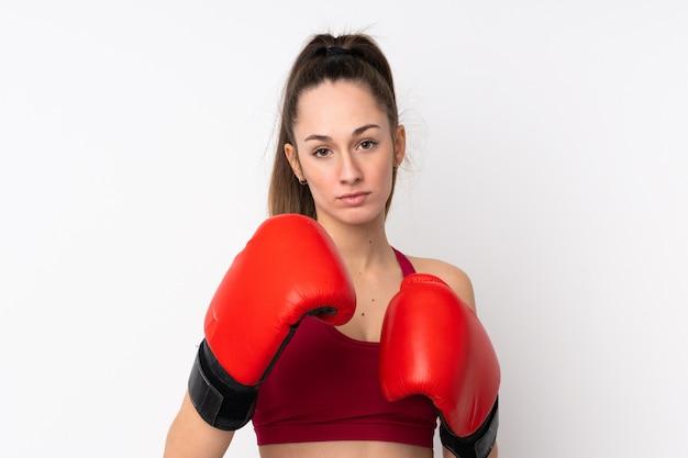 Junge sportbrünette frau über isolierte weiße wand mit boxhandschuhen