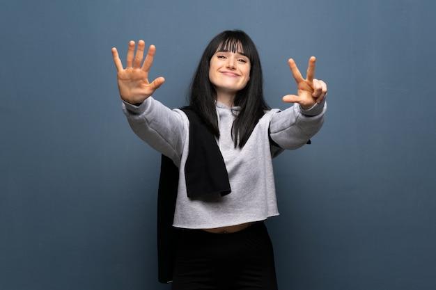 Junge sportfrau, die acht mit den fingern zählt