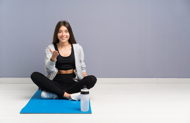 Junge sportfrau, die auf dem boden mit dem mattenhändeschütteln nach viel sitzt
