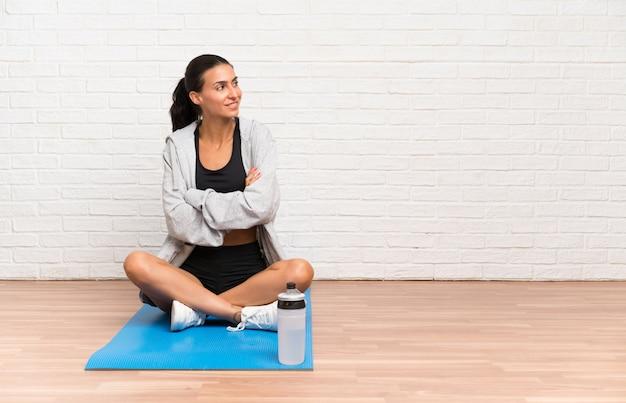 Junge sportfrau, die auf dem boden mit dem mattenlachen sitzt