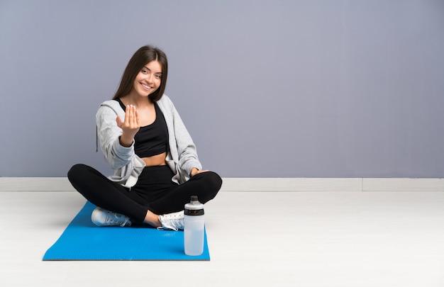 Junge sportfrau, die auf dem boden mit der matte einlädt zu kommen sitzt