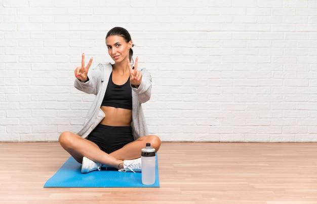 Junge sportfrau, die auf dem boden mit der matte lächelt und zeigt siegeszeichen sitzt