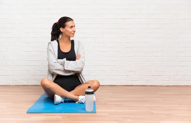 Junge sportfrau, die auf dem boden mit der matte schaut zur seite sitzt