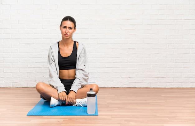 Junge sportfrau, die auf dem boden mit der matte traurig sitzt
