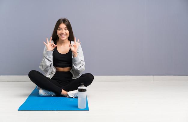 Junge sportfrau, die auf dem boden mit der matte zeigt ein okayzeichen mit den fingern sitzt
