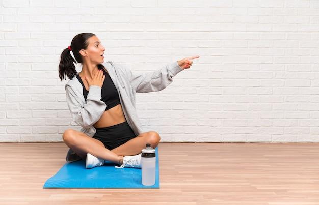 Junge sportfrau, die auf dem boden mit der matte zeigt finger auf die seite sitzt
