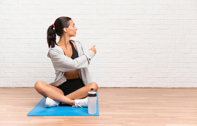 Junge sportfrau, die auf dem boden mit der matte zurück zeigt mit dem zeigefinger sitzt