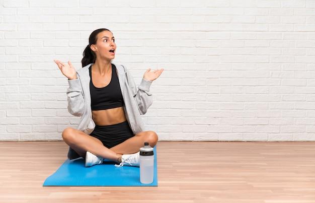 Junge sportfrau, die auf dem boden mit matte mit überraschungsgesichtsausdruck sitzt