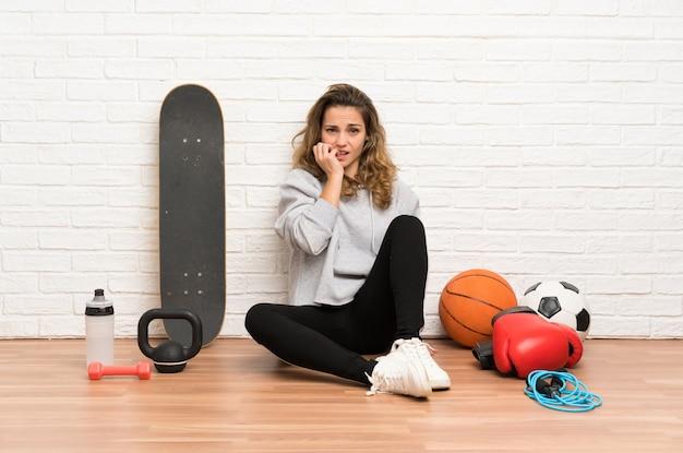 Junge sportfrau, die auf dem boden nervös und erschrocken sitzt