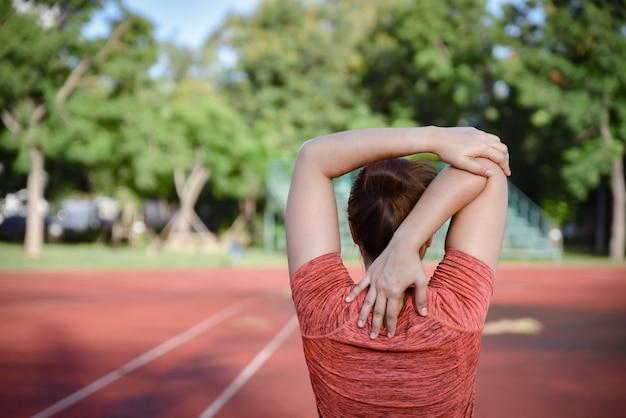 Junge sportfrau, die auf stadionsbahn bevor dem laufen ausdehnt.