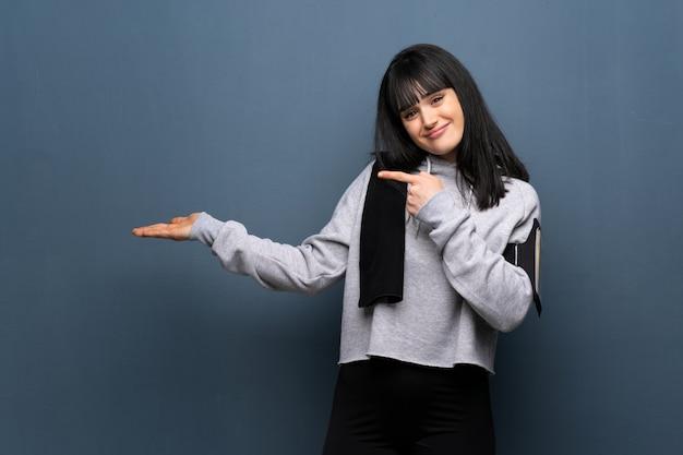 Junge sportfrau, die copyspace eingebildet auf der palme hält, um eine anzeige einzufügen