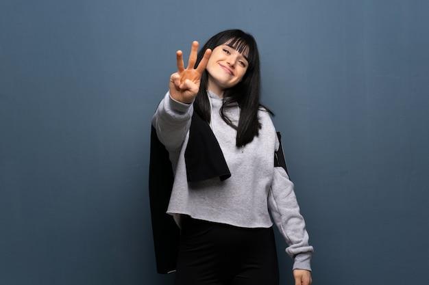 Junge sportfrau, die drei mit den fingern glücklich und gezählt worden sein würden