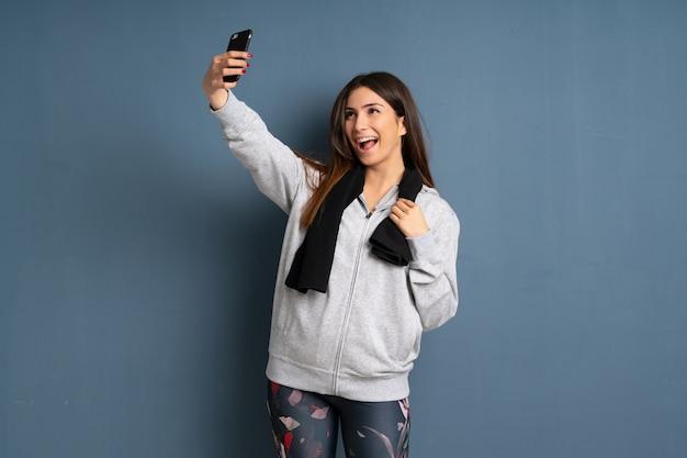 Junge sportfrau, die ein selfie macht
