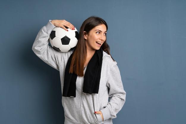 Junge sportfrau, die eine fußballkugel anhält
