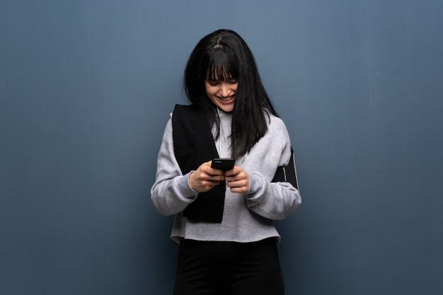 Junge sportfrau, die eine mitteilung mit dem mobile sendet