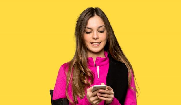 Junge sportfrau, die eine mitteilung mit dem mobile über getrenntem gelb sendet