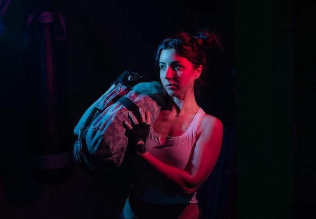 Junge sportfrau, die eine schwere eignungstasche für das training im blauen rotlicht des neongradienten über einem funktionswandkonzept der dunklen wand hält