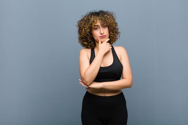 Junge sportfrau, die ernst, verwirrt, unsicher und nachdenklich aussieht und unter optionen oder entscheidungen gegen graue wand zweifelt