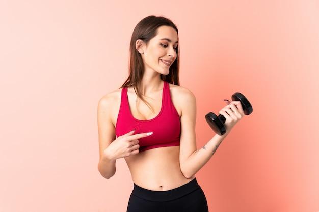 Junge sportfrau, die gewichtheben über isolierte rosa wand macht, die einen sieg feiert