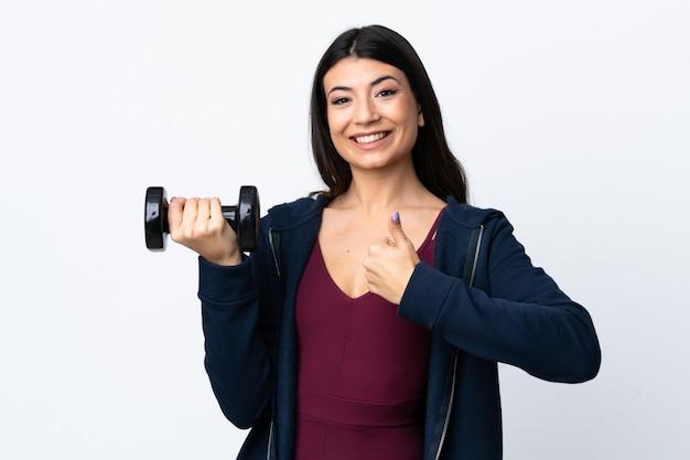 Junge sportfrau, die gewichtheben über weiße wand mit daumen nach oben macht, weil etwas gutes passiert ist