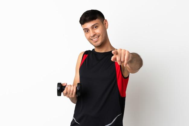 Junge sportfrau, die gewichtheben zeigt finger auf sie mit einem selbstbewussten ausdruck