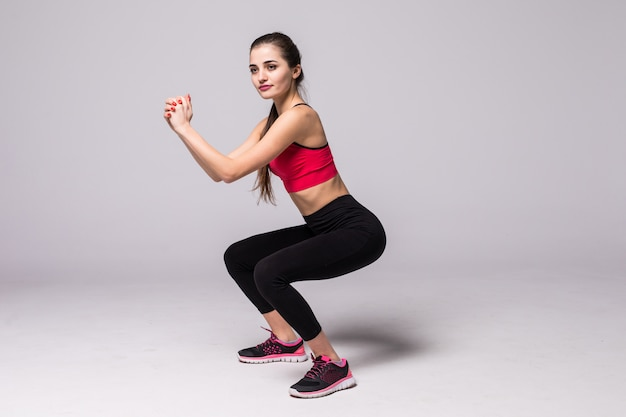 Junge sportfrau, die kniebeugen mit hanteln auf grauer wand tut