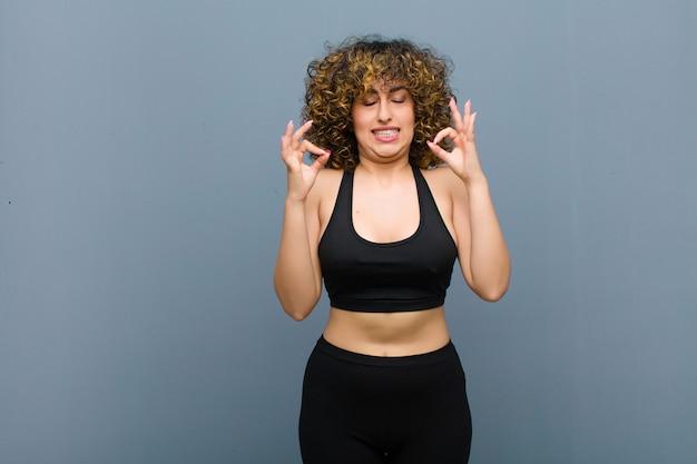 Junge sportfrau, die konzentriert und meditierend aussieht, sich zufrieden und entspannt fühlt, an graue wand denkt oder eine wahl trifft