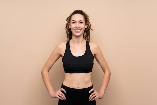 Junge sportfrau, die mit den armen an der hüfte und am lächeln aufwirft