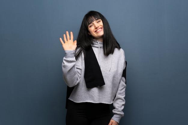 Junge sportfrau, die mit der hand mit glücklichem ausdruck begrüßt