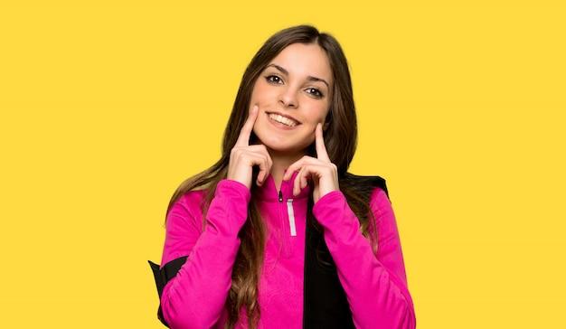 Junge sportfrau, die mit einem glücklichen und angenehmen ausdruck über lokalisiertem gelbem hintergrund lächelt