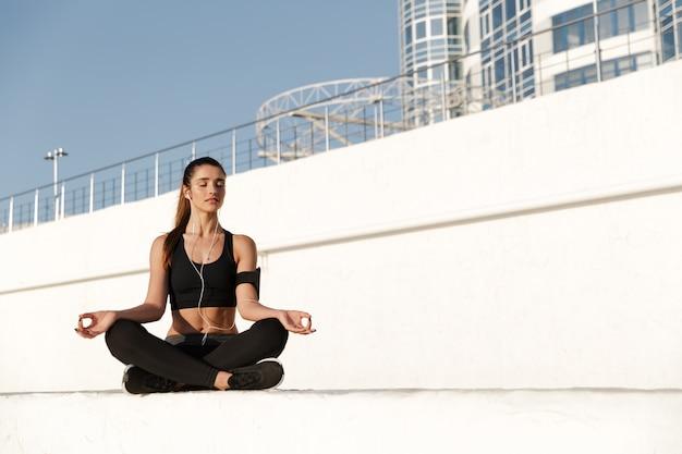 Junge sportfrau, die musik mit kopfhörern hört, machen yogaübungen.