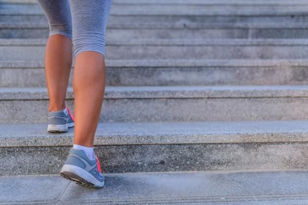 Junge sportfrau, die oben auf stadttreppe läuft
