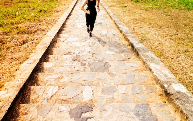 Junge sportfrau, die oben im freien auf blauem himmel läuft
