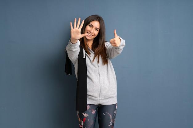 Junge sportfrau, die sechs mit den fingern zählt