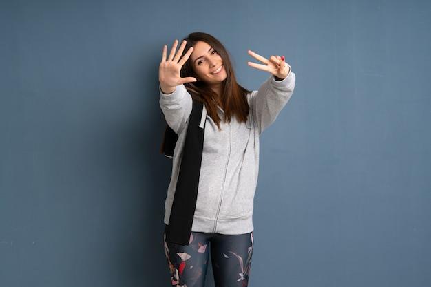 Junge sportfrau, die sieben mit den fingern zählt