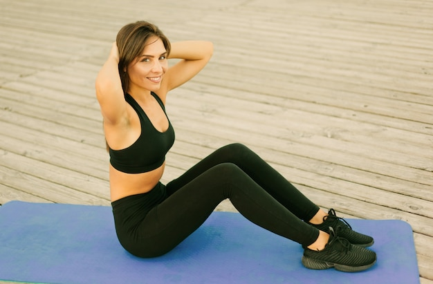Junge sportfrau, die übung für bauchmuskeln tut