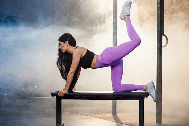 Junge sportfrau, die übung unter verwendung der bank im fitnessstudio macht.