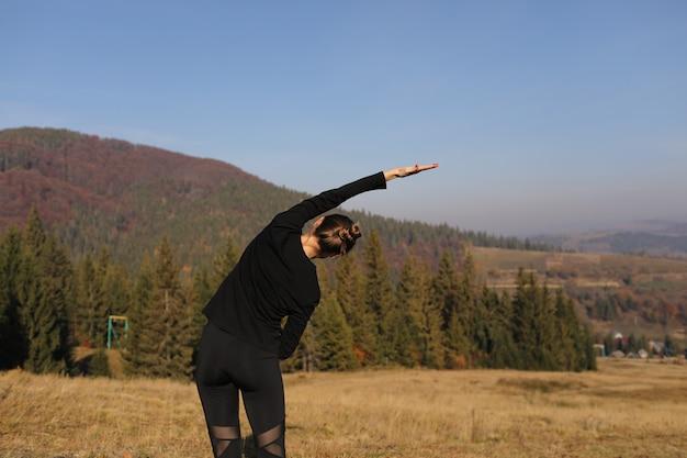 Junge sportfrau, die yogaübung auf den bergen und himmel im herbst tut