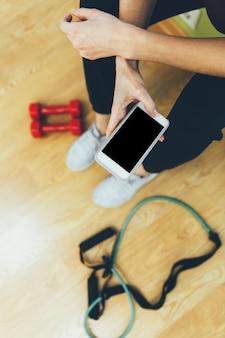 Junge sportfrau in der turnhalle unter verwendung des smartphone, eignung, lebensstilkonzept ausbildend