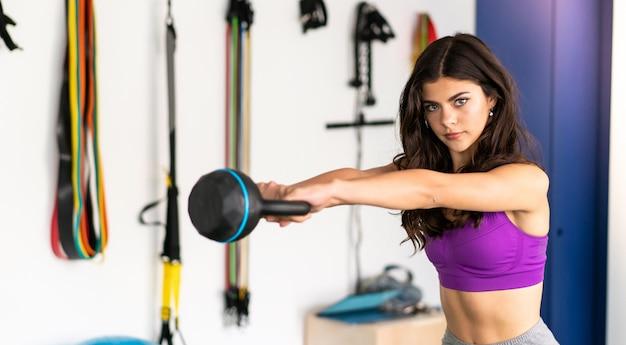 Junge sportfrau in einer turnhalle mit kettlebell