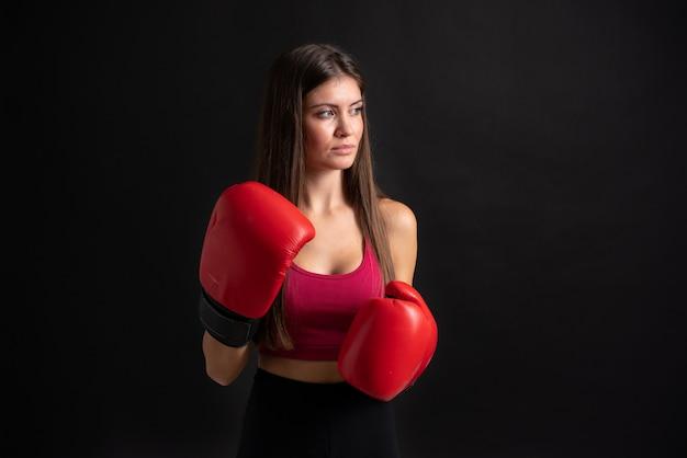 Junge sportfrau mit den boxhandschuhen über lokalisiert