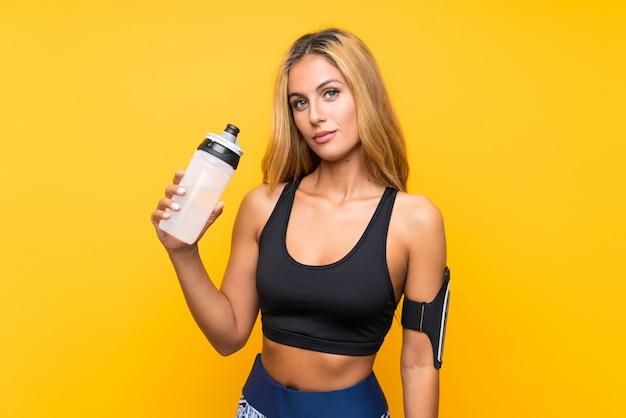 Junge sportfrau mit einer flasche wasser