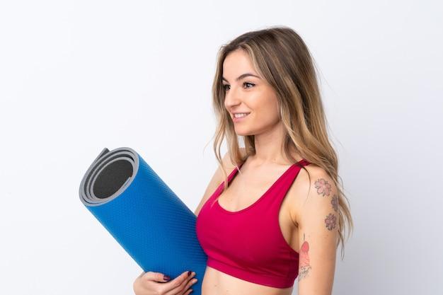 Junge sportfrau mit einer matte
