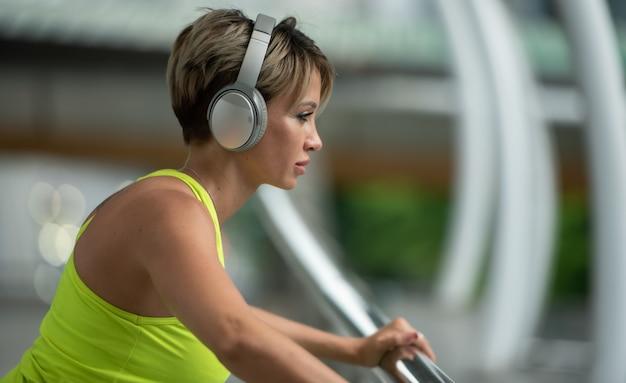 Junge sportfrau mit kopfhörern hörend musik für entspannen sich während übung.
